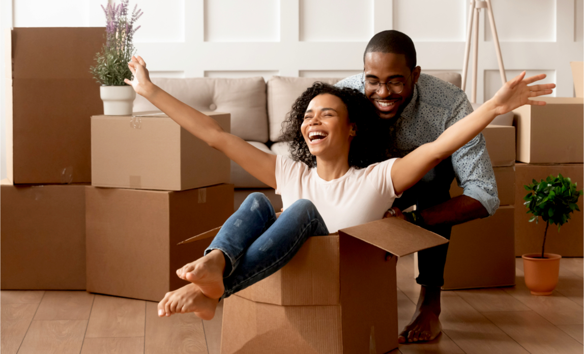 A young excited couple move into their first home after buying it using Right to Buy.