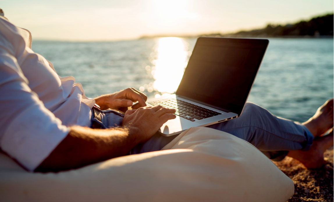 A business man is working on his laptop whilst sitting on the beach