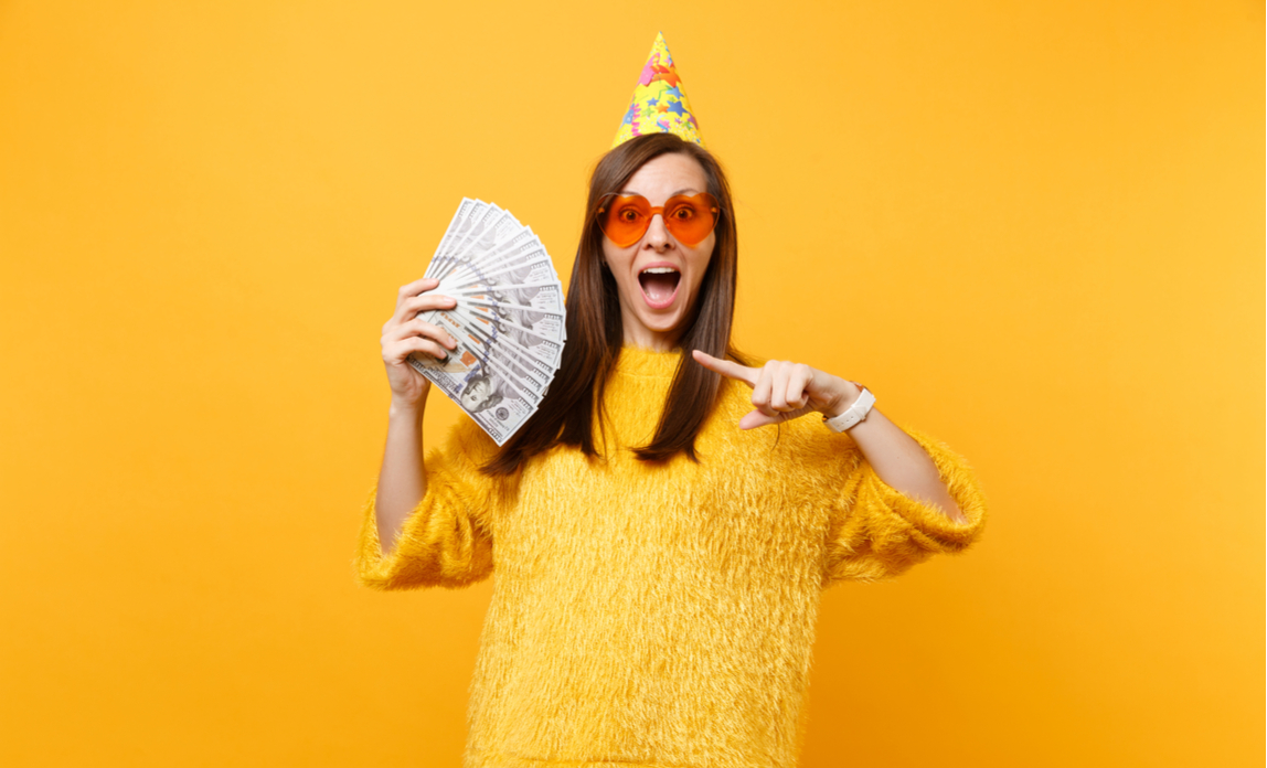 Woman wearing a birthday hat is pointing at a bundle of money in her hand representing a birthday windfall