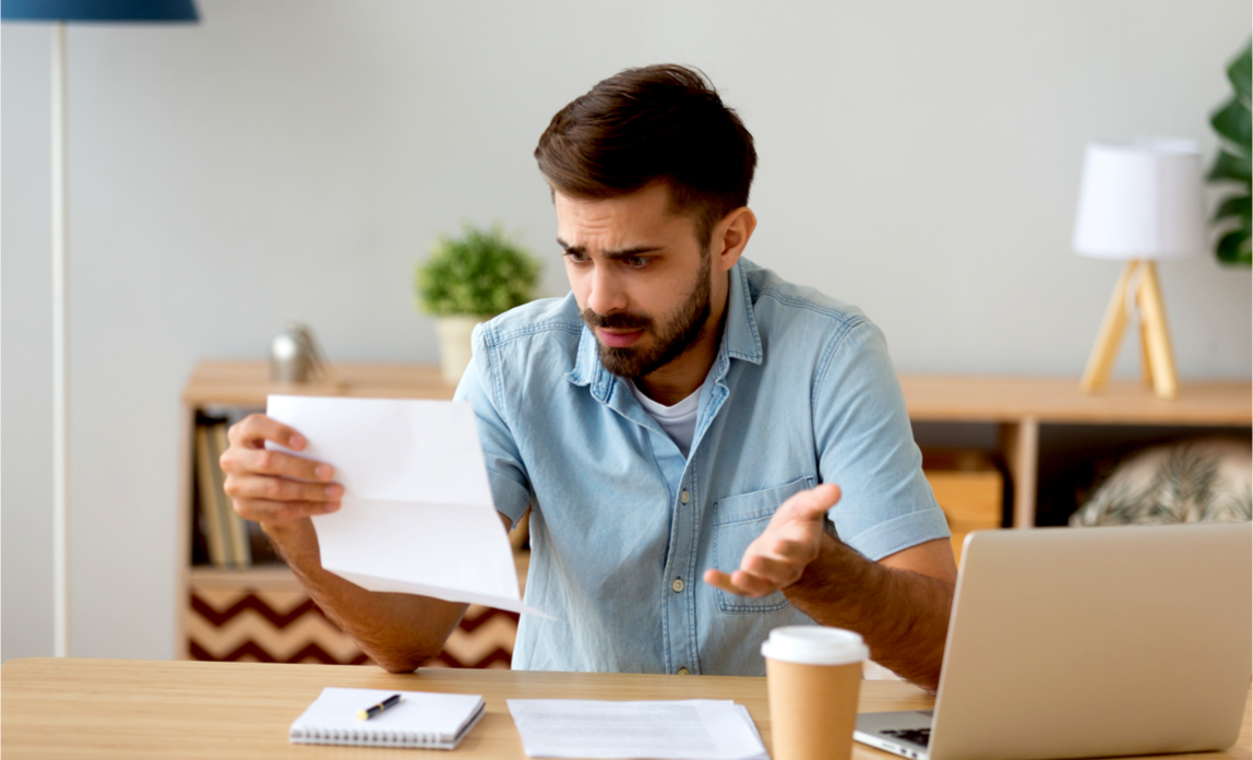 A young landlord is frustrated and confused looking at a tax letter from HMRC.