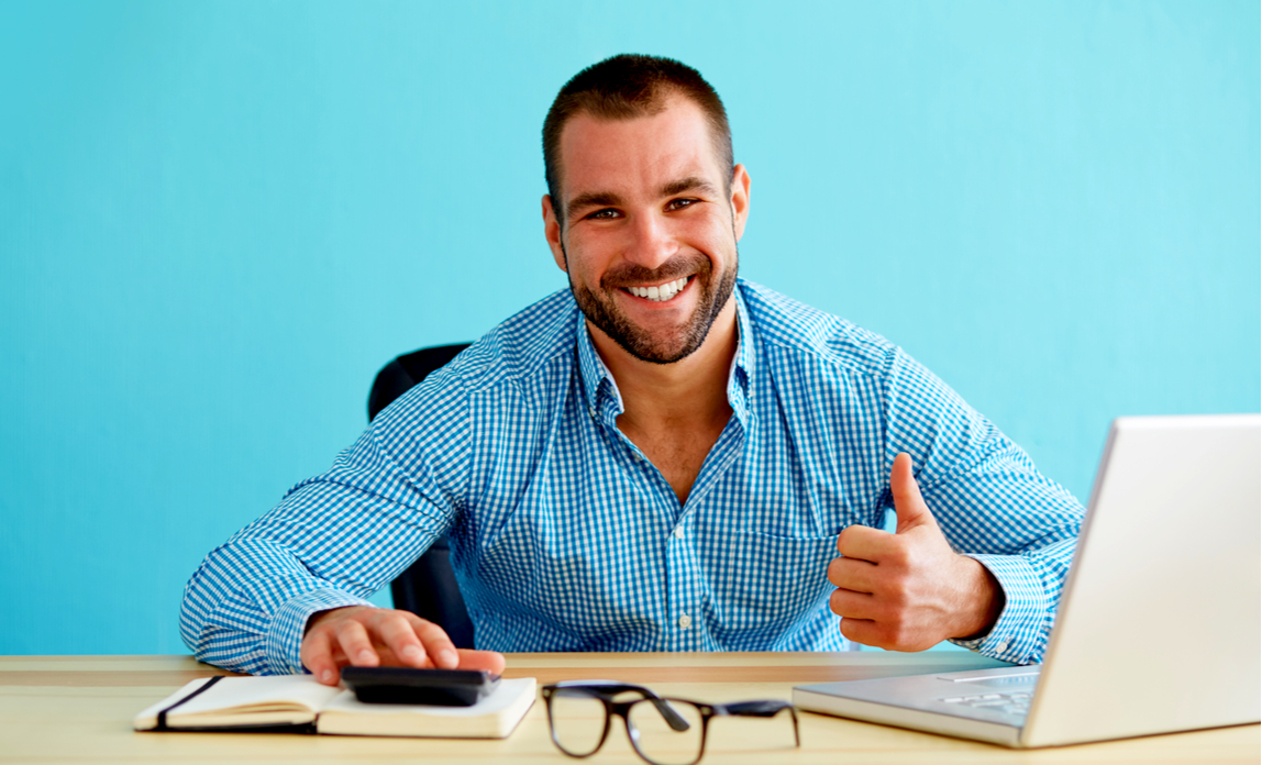 A happy business owner calculates his tax savings and gives a thumbs up.
