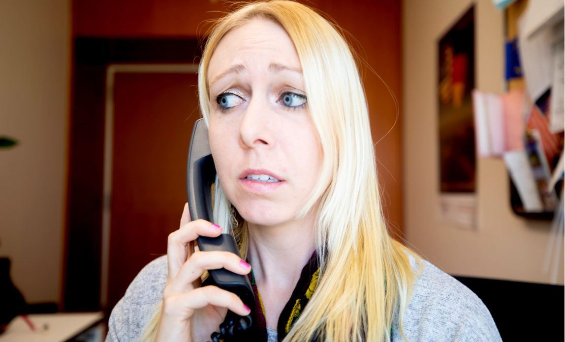 A young woman looks worried when she answers the phone in her office