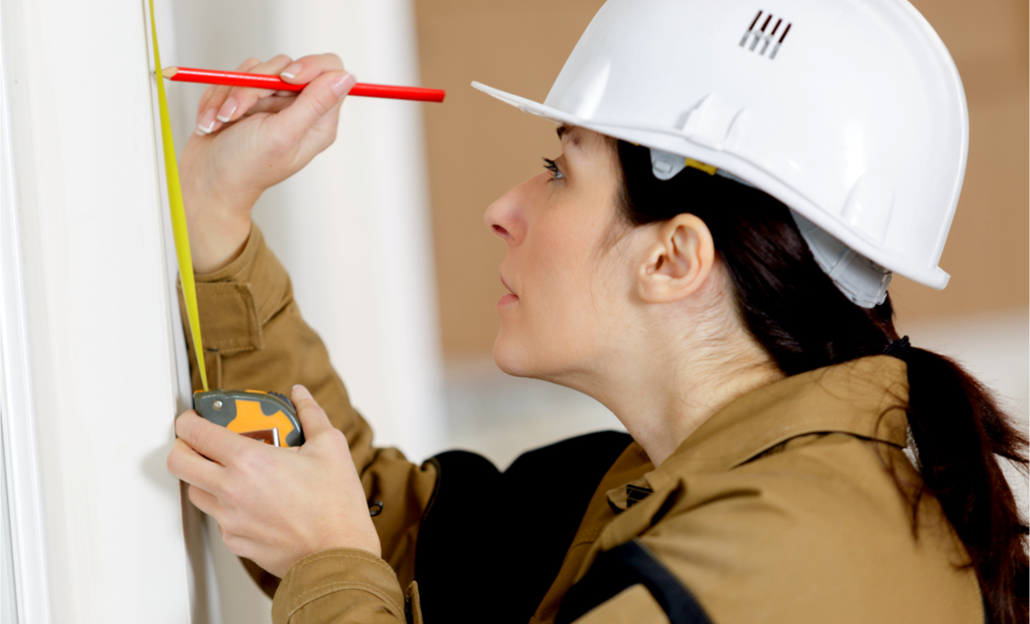 An on-site tradeswoman takes a measurement using a retractable tape measure