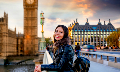 A happy US expat pictured on Westminster Bridge in London - working abroad concept.