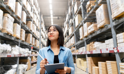 A female auditor completes a stocktaking inventory in warehouse