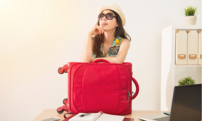 Cheerful office worker with luggage and sunglasses ready for long vacation holiday.