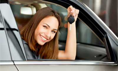 A businesswoman happily holds up the keys to her new car, after getting car finance despite a poor credit score.