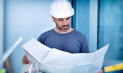 Worker in white hard-hat looking at big sheet of paper