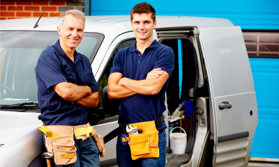 Two tradesman in blue tops stood beside a grey van