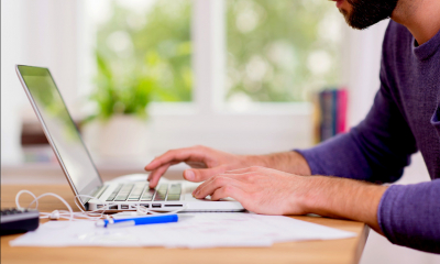 Man in blue top working from home using a laptop