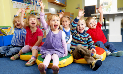 Group of children at childcare raising their hands