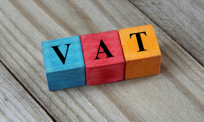 Three multicoloured wooden blocks with 'VAT' written on them