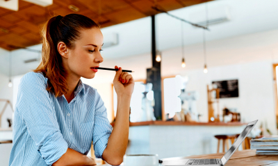 Female in blue shirt biting pencil considering freelance insurance