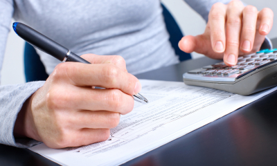 Person in a grey top holding a pen working out their corporation tax using a calculator