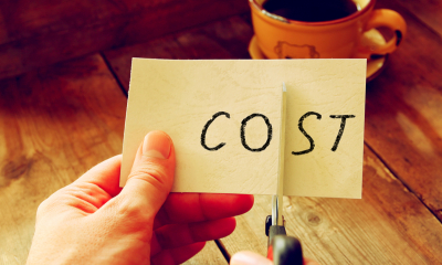 A man cuts a piece of paper with the word cost written on it