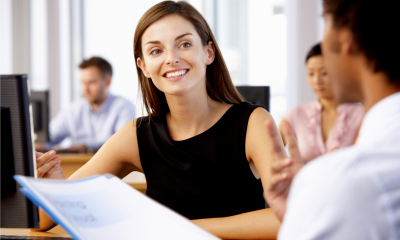 Smiling woman in a black top discussing employee insurance with an employee