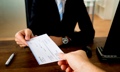 Man in a suit sat at a desk handing an employee an employment allowance slip