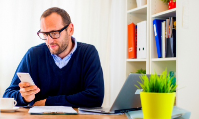 Bearded man in a blue sweater wearing glasses looking at his phone sat at a desk