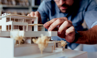 An architect puts the finishing touches to a model building - planned construction project.