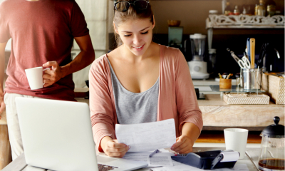 A happy business owner checks her loan and interest statement at her desk.