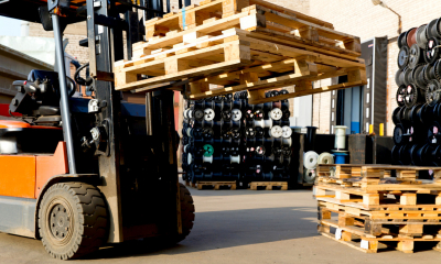 Forklift lifting up multiple wooden pallets with other pieces of machinery in the background