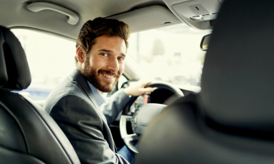 Man in a suit smiling at the camera while driving his company car