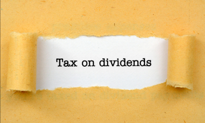 Ripped yellow paper exposing 'Tax on dividends' written on white paper
