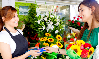 A female customer pays for her flowers in a florists using a card payment