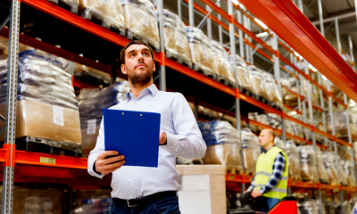 Man checking stock in large logistics warehouse