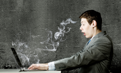 A man in a suit typing at a laptop that has smoke coming out of it
