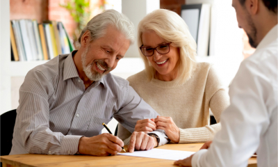 A happy, older couple receive financial planning advice