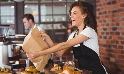 Laughing barista giving paper bag to customer at coffee shop