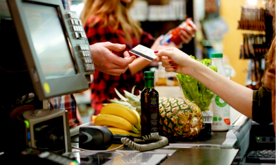 Man purchasing food at a supermarket using his credit card