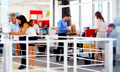 Multiple different people stood in an open-plan styled office