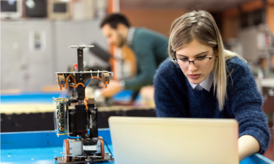 Woman in a blue jumper and glasses working on a project at her engineering firm