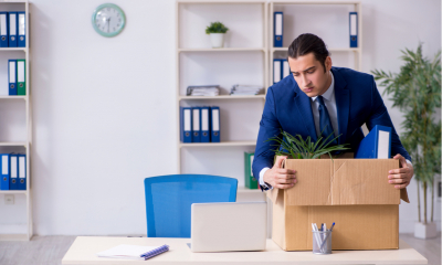 Employee putting all of his work belongings into a cardboard box