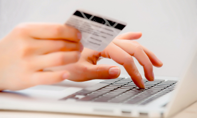 Using laptop, holding credit card - Pay your VAT bill