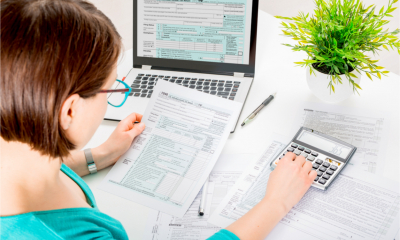 A small business owner fills in her Self Assessment tax return, using a calculator to work out key figures.