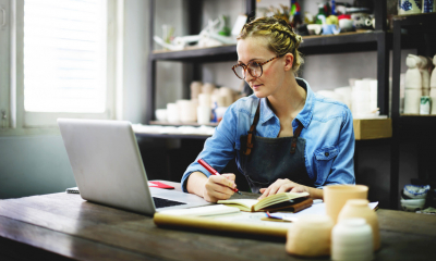 Woman in blue shirt and black apron writing in a notebook and looking at a laptop