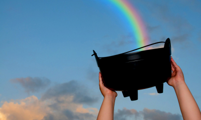 Person holding up a black bucket to the sky with a rainbow in the background
