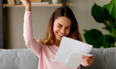 An attractive women celebrates receiving confirmation of her tax refund