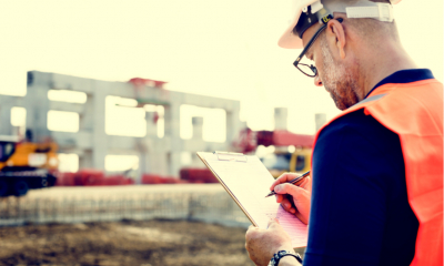 An architect makes notes on a building site where a new property is being built.