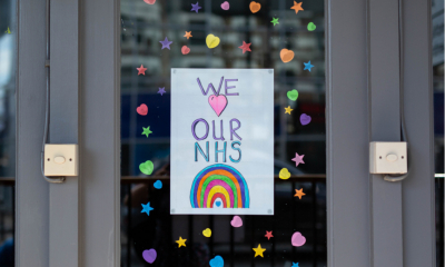 We love our NHS sign with rainbow and pink heart banner hanged on the window decorated with colorful stickers on display of closed restaurant