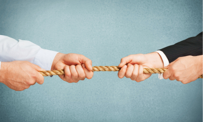 Two businessmen in a tug of war, blue background