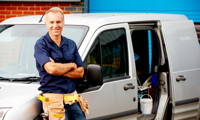 A self-employed man stands next to his work van