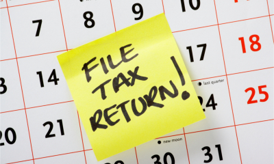 A yellow sticky note on a calendar marked 'File Tax Return!'