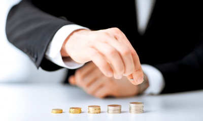 Arm in suit sleeve sorting piles of coins
