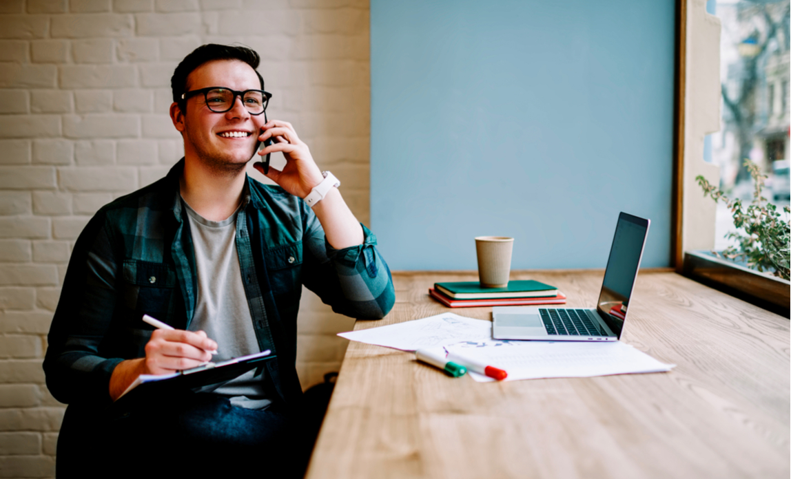 Cheerful male freelancer making telephone call