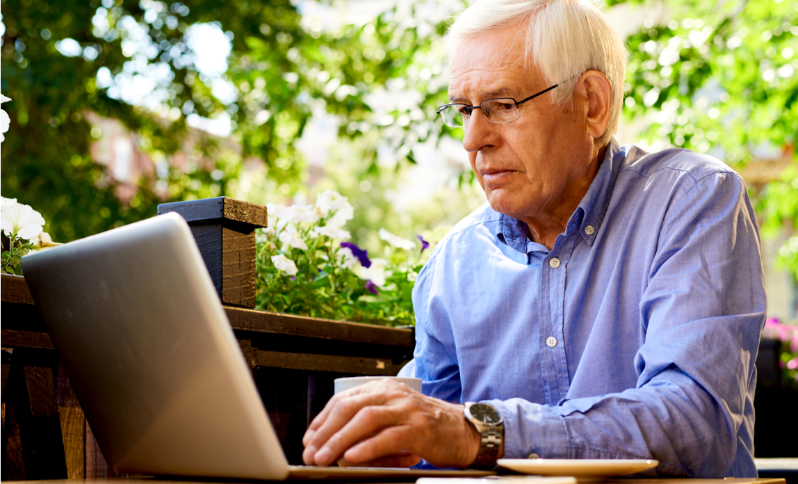 Senior man working with laptop in outdoor cafe
